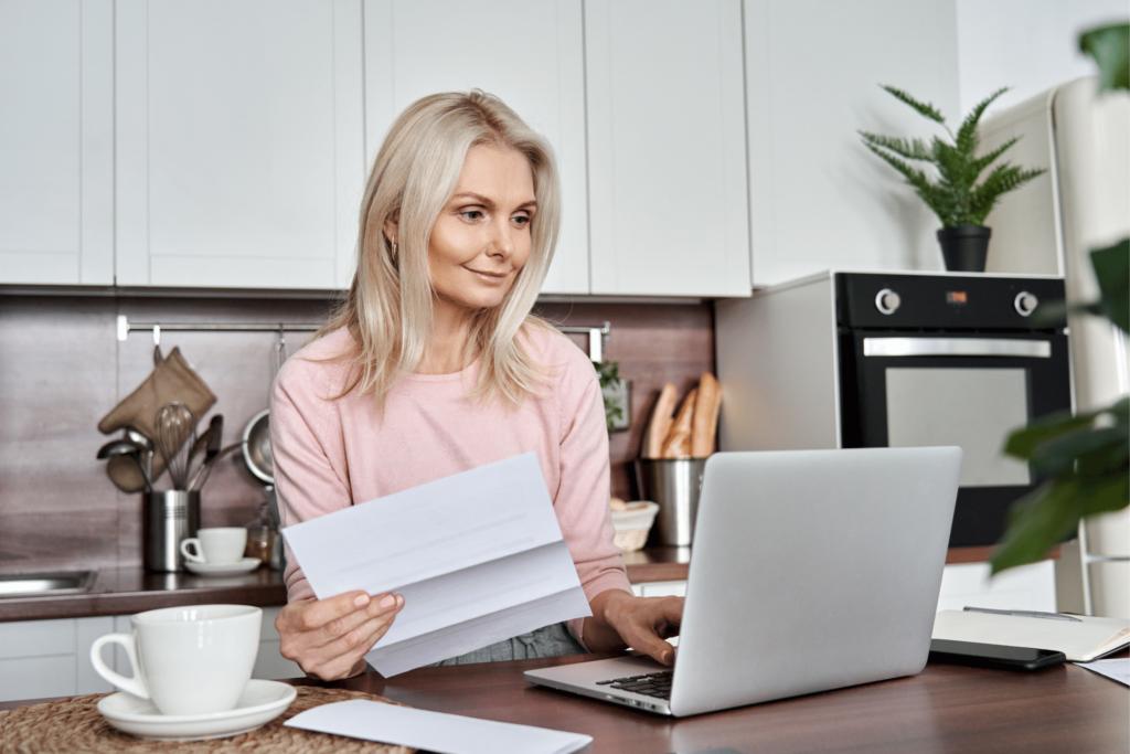 woman holding paper bill using laptop